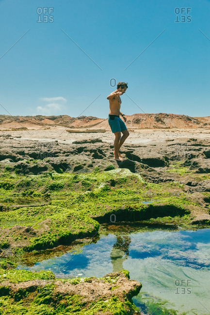Young man exploring ocean bluffs during the summer in Baja, Mexico.