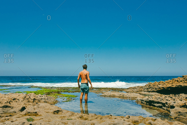 Young man standing in water looking out to ocean from bluffs in Baja