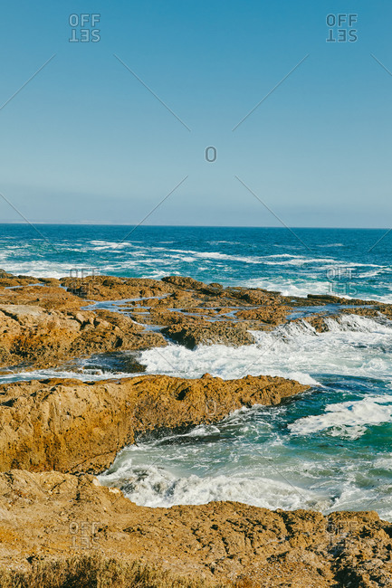 Pacific ocean waves breaking against bluffs in Baja, Mexico.