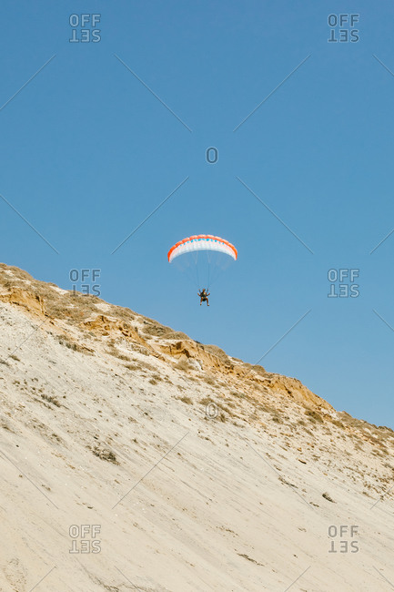 Young man paragliding during sunset off cliffs in Baja, Mexico.