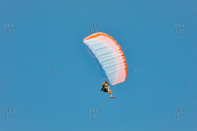 Young man paragliding during summer off cliffs in Baja, Mexico.