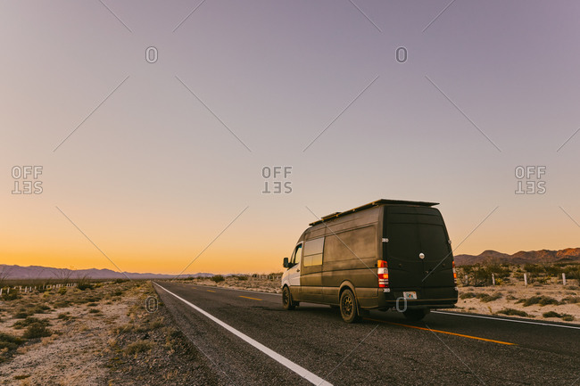 Camper van on isolated highway during sunset in desert of Mexico.