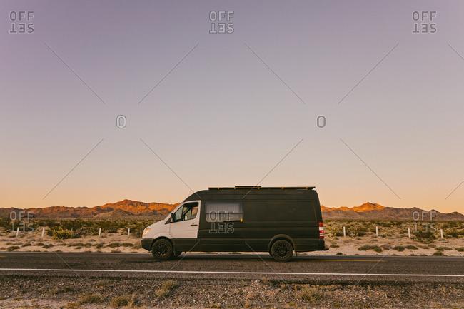 Camper van on highway during sunset in desert of Baja, Mexico.