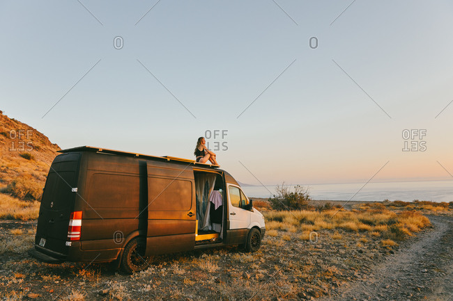 Young woman on camper van looking out to the sunrise in Baja, Mexico.
