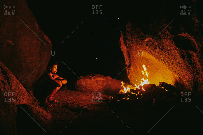Young man in front of camp fire at night in northern California.