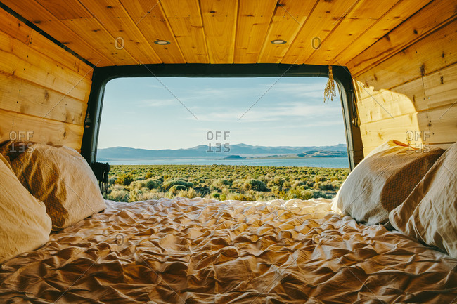 View of mono lake from open doors of camper van with bed in California