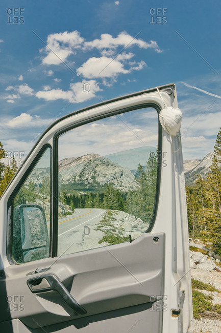 Open camper van door and mask on highway in Yosemite National Park.