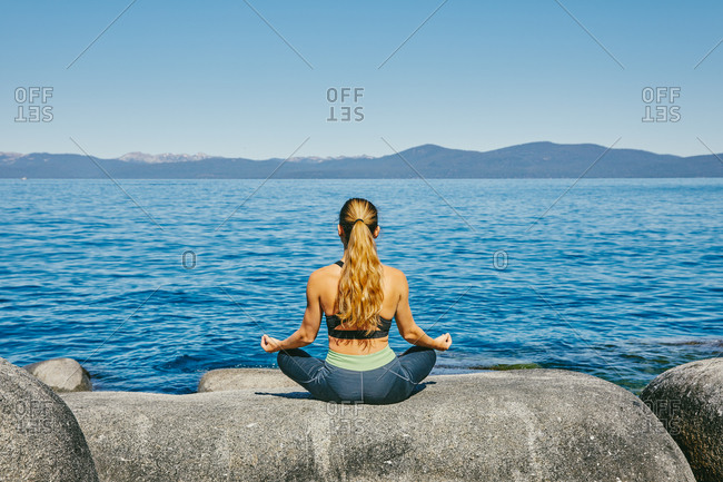 Young woman practicing yoga on Lake Tahoe in northern California.