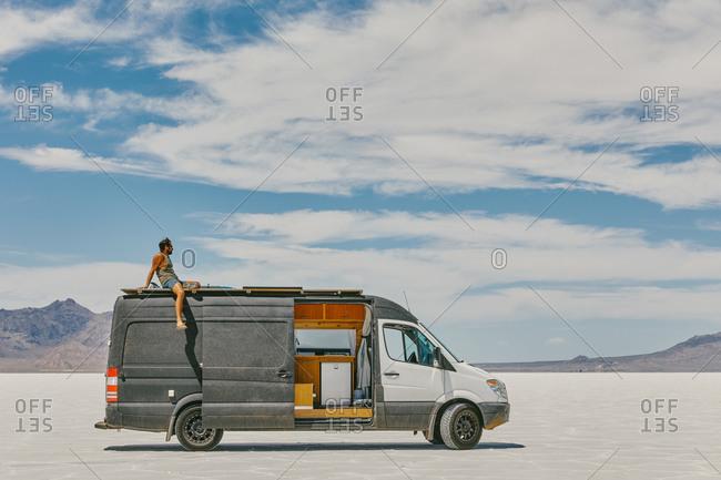 Young man sitting on roof of camper van in Bonneville Salt Flats.