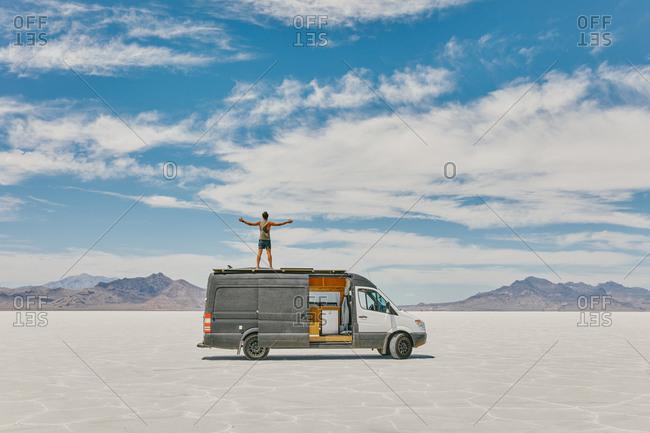 Young man standing on roof of camper van in Bonneville Salt Flats.