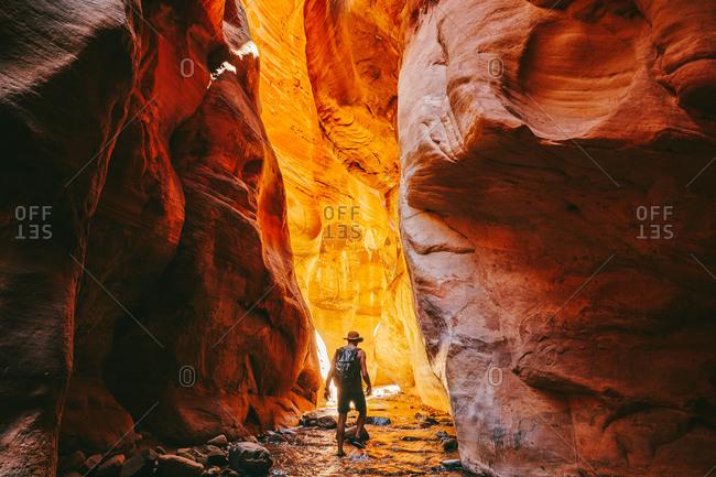 Young man wearing a hat, exploring a slot canyon in Kanarra Fall, Utah