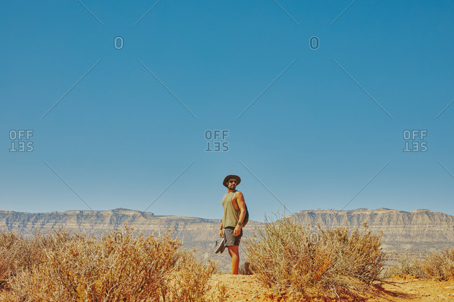 Back of young man wearing hat gazing out to desert during hike.