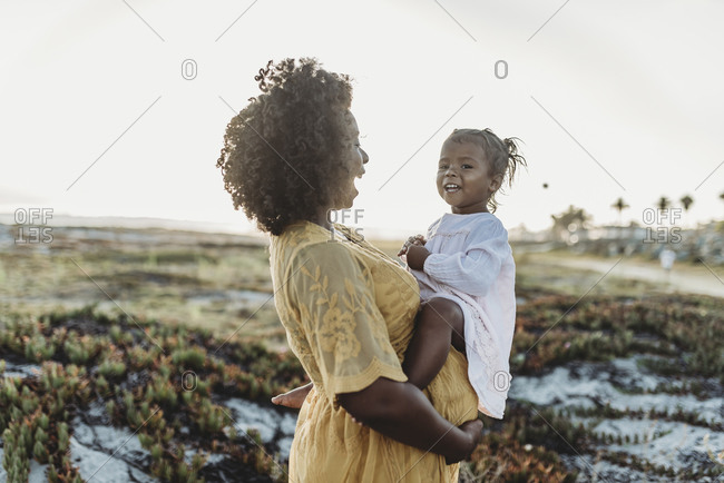 Pregnant mother holding young toddler girl on belly at beach