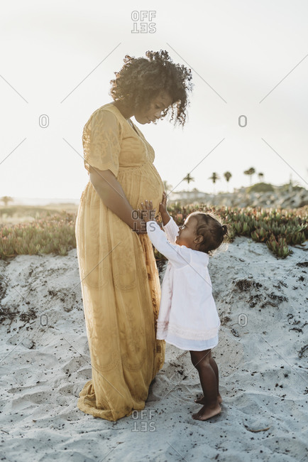 Full length view of young toddler girl with mother's pregnant belly
