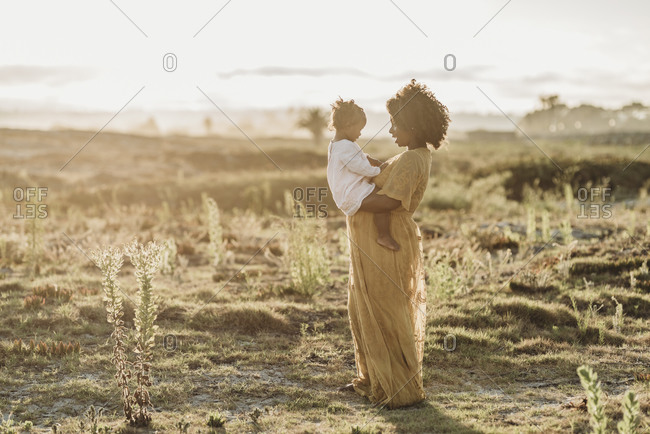 Full length view of pregnant mother holding young toddler girl on bell