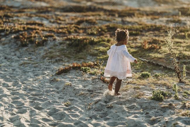 Behind view of little girl running away at beach