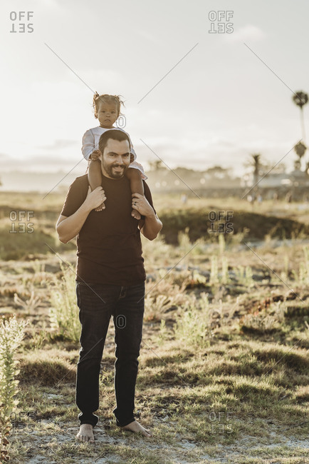 Portrait of young father and toddler girl smiling at the beach
