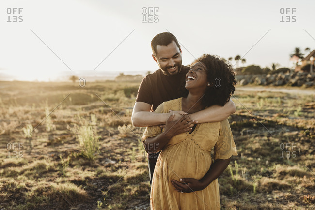 Young married couple embracing pregnancy at beach
