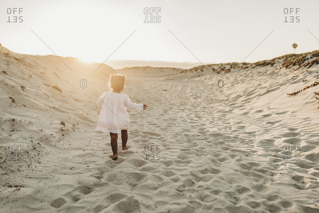 Young girl walking away at beach during sunset