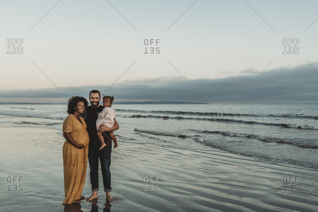 Portrait of family of three smiling at the beach