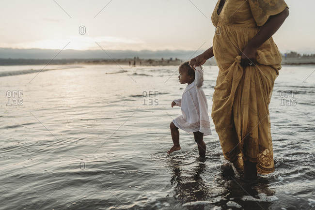Young daughter and pregnant mother walking into the ocean