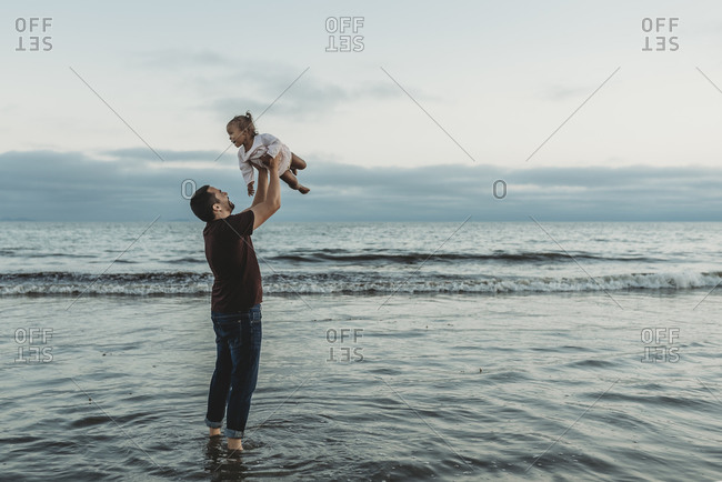 Dad throwing his daughter in air in the ocean