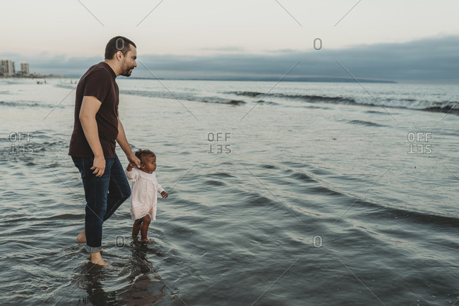 Toddler daughter and young father walking into the ocean