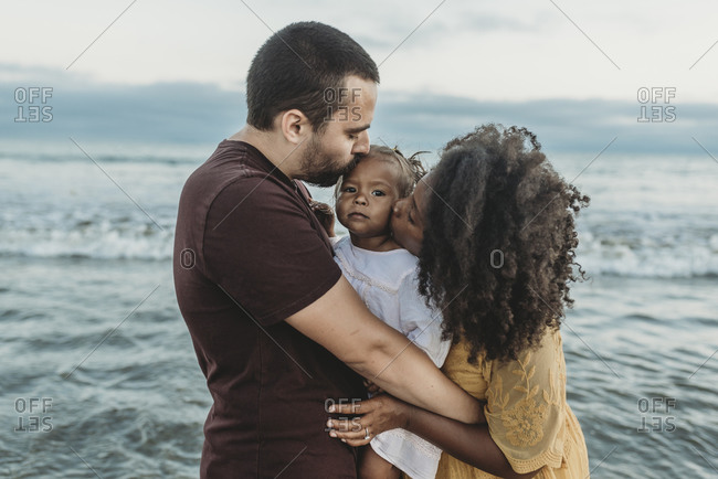 Parents kissing young toddler in the ocean