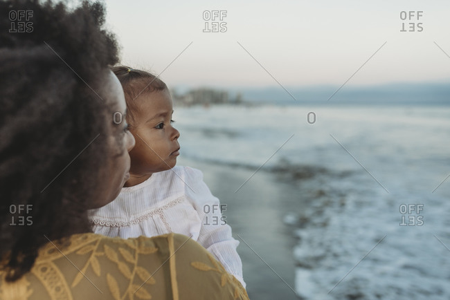 Side view of mother and daughter embracing in the ocean