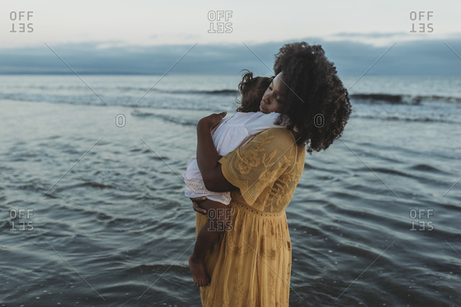 Side view of mother and daughter hugging in the ocean