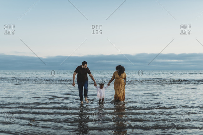 Landscape view of young family of three walking together in the ocean