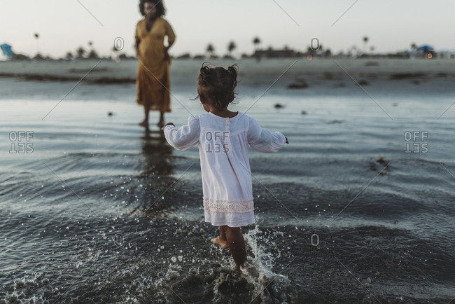 Young toddler girl splashing in the sea with family