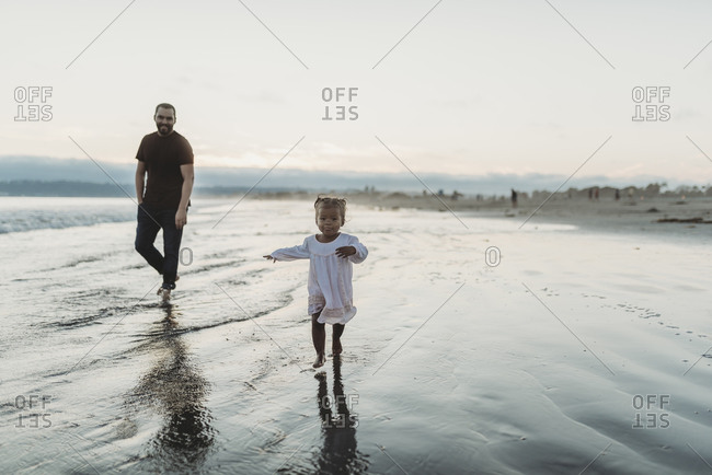Young toddler girl running on the beach with dad in ocean