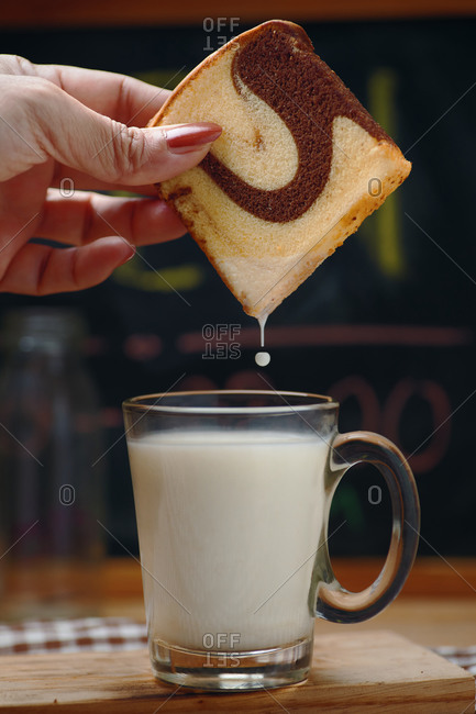 The woman's hand dip the marble cake into the milk in a glass of milk