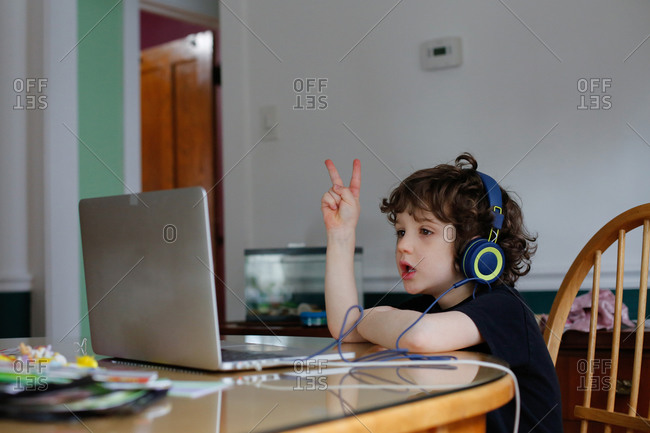 A young boy learning in front of a laptop