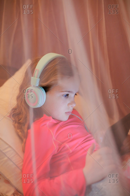 A young girl learning in front of a tablet while laying in bed