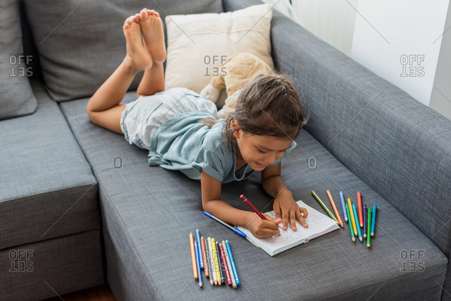 Hispanic girl painting on a sofa with pencil colors.