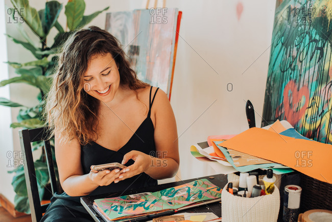 Female painter using smartphone while working on paintings in studio