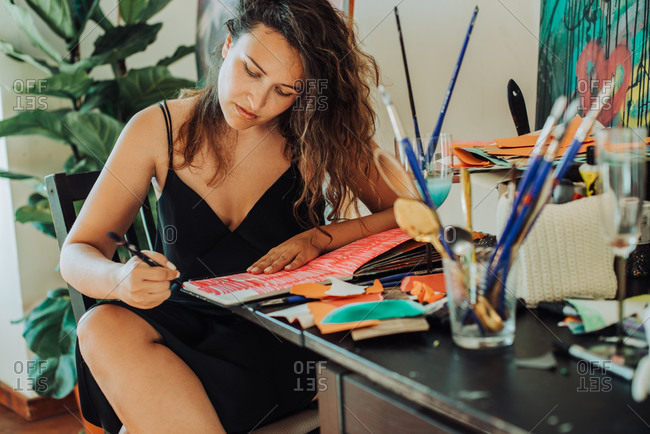 Woman painter focused on work sitting at table in her studio