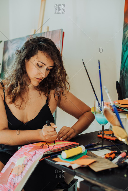 Woman painter focused on work sitting at table in her studio, close up