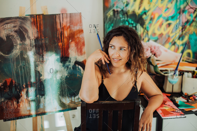Young female artist sitting at art studio with canvas on background