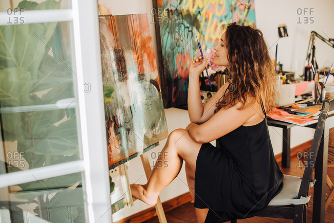 Female visual artist working on canvas in studio making abstract art