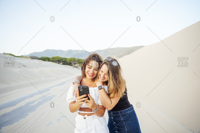 Young women with mobile phones are excited and happy