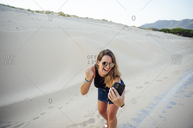 Young woman with mobile cell phone is excited and joy