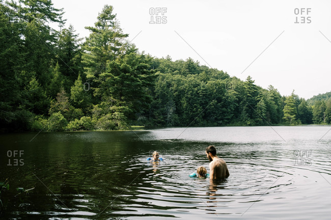 A father and his children cooling off in a hidden swimming hole