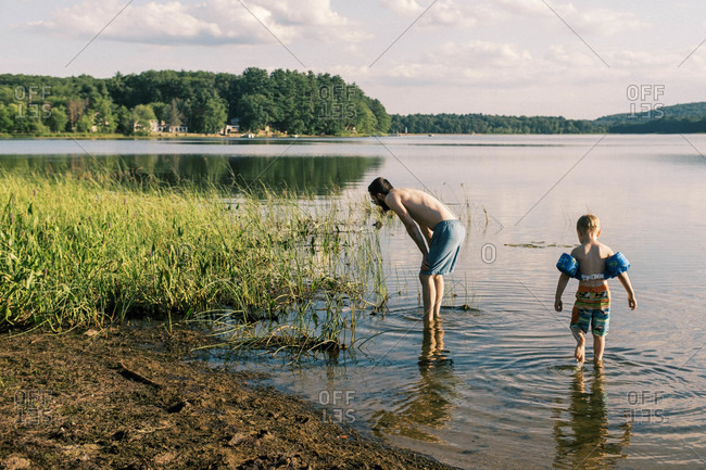 A father and son looking for fish by the shore