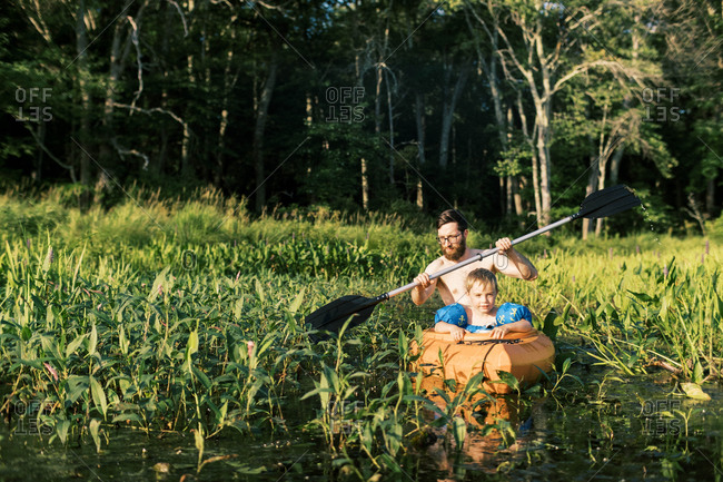 A father and son exploring a marsh in their kayak