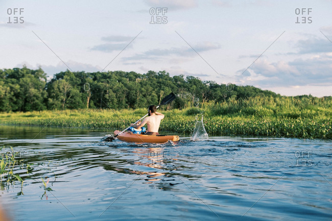 A father and son traveling a river together in their kayak at sunset