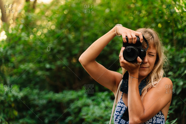 Blonde woman taking a picture standing in a park