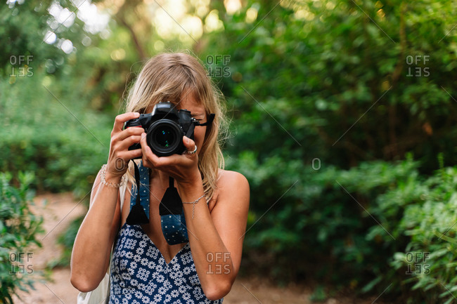Woman taking a picture standing in a park